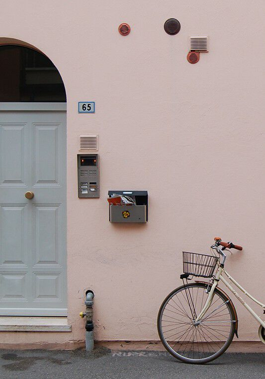 Bike leaning on blush wall in Italy