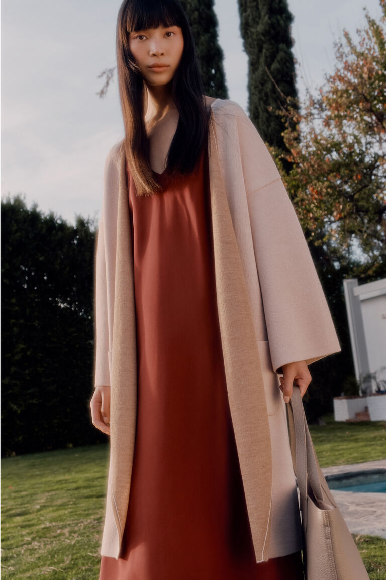 Model wearing Reversible Knitted Coat, Silk Slip Dress, and Small Tote Bag
