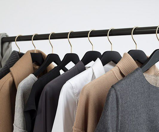 Cuyana tops hanging on clothing rack
