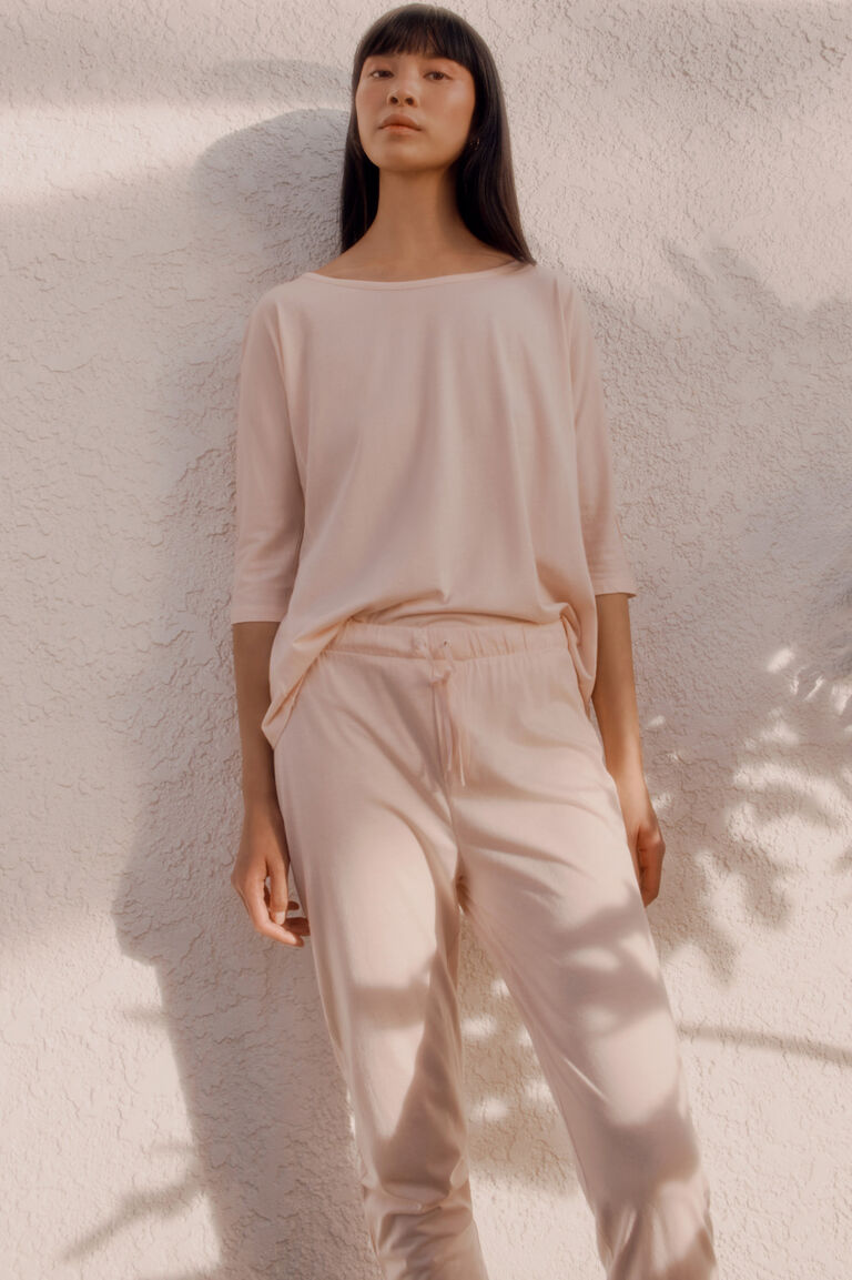 Model wearing Cuyana Drape-Back Top and Tapered Pant