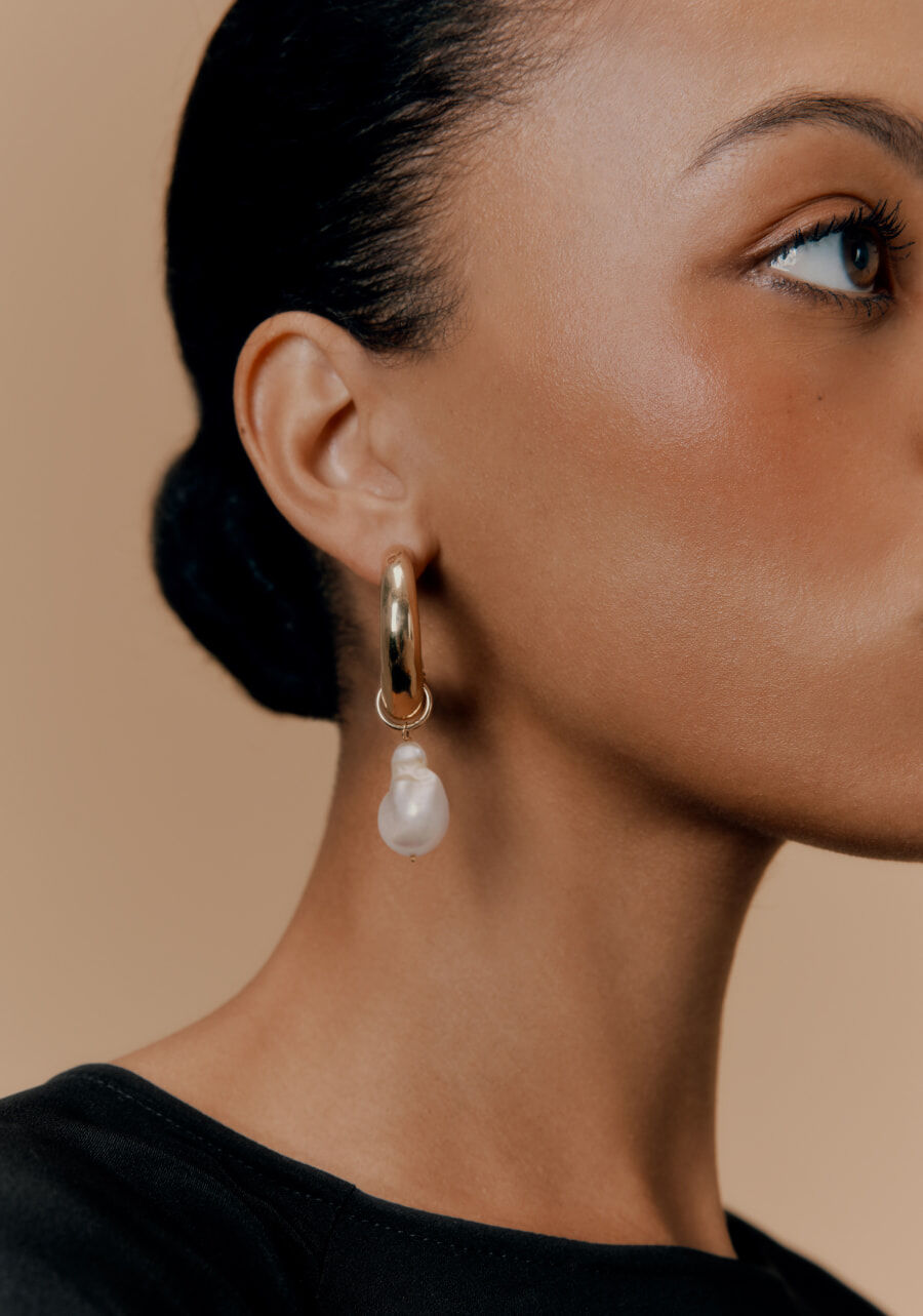 Detail shot of model wearing Crescent Hoop Earrings with Pearl Embellishments