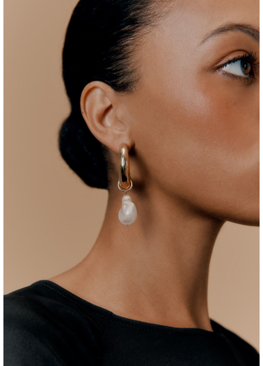 Model wearing Cuyana Crescent Hoop Earrings with Baroque Pearl Embellishment