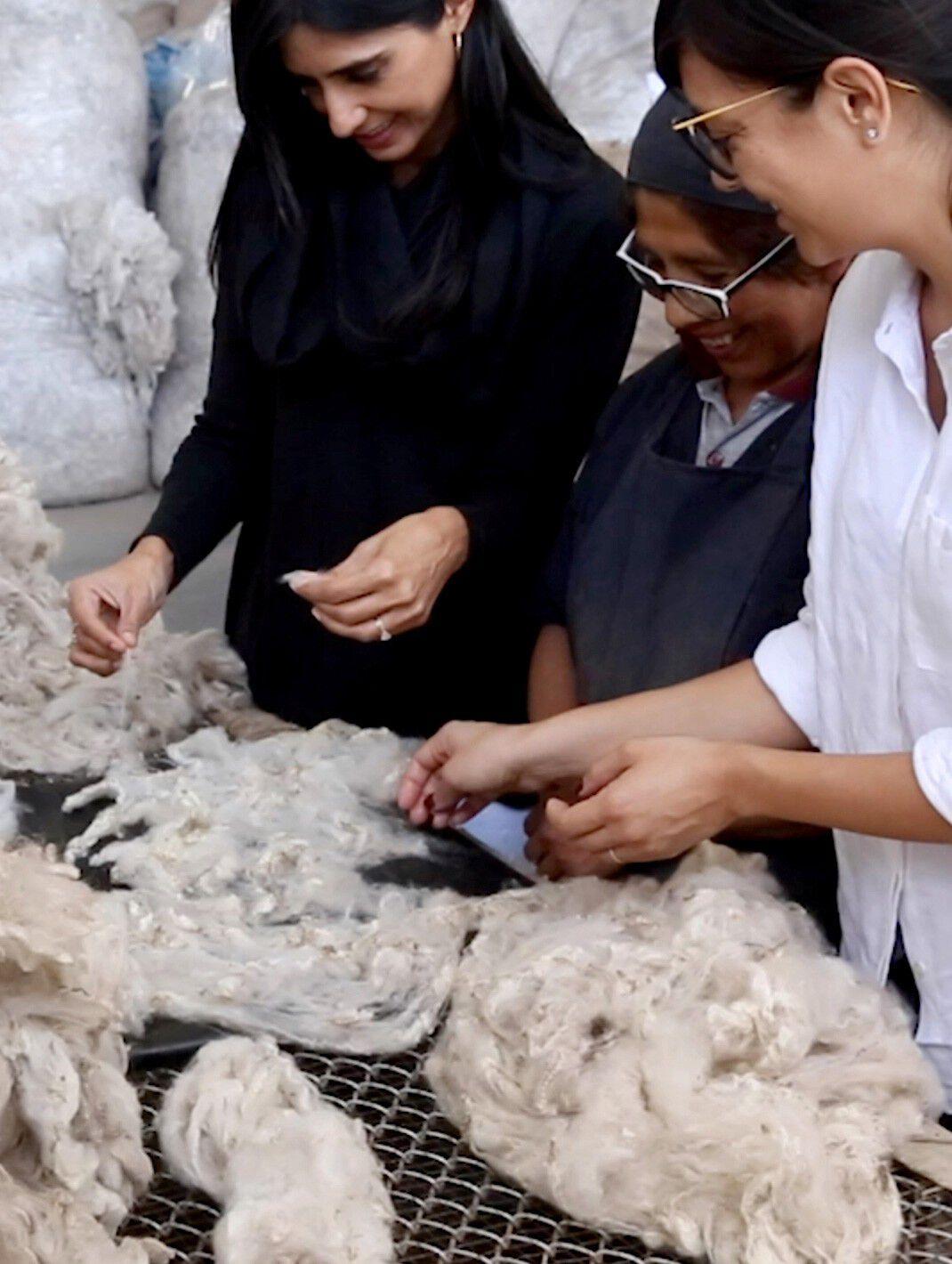 Karla & Shilpa with woman sorting alpaca fibers