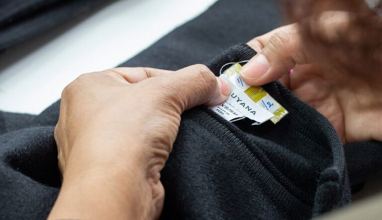 Woman sewing Cuyana label into sweater