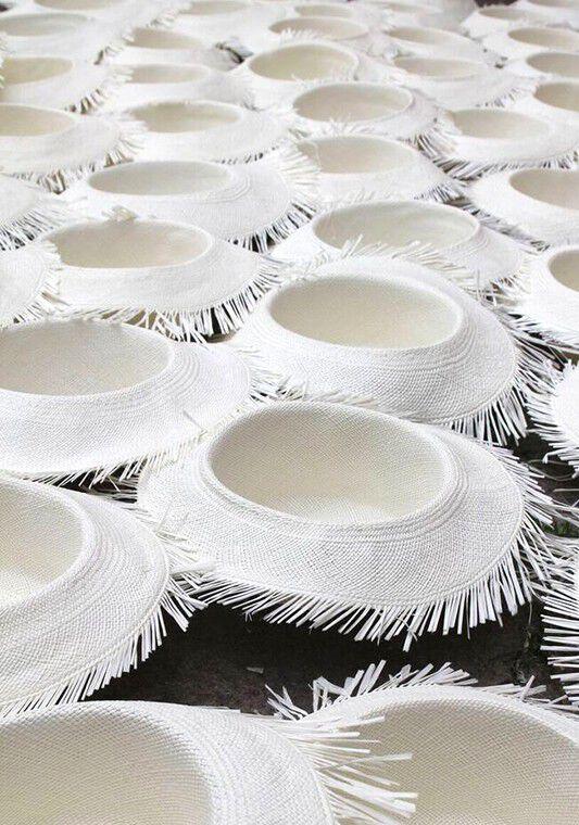 many toquilla straw hats half woven
