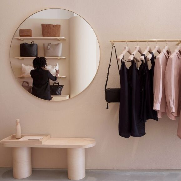 Cuyana Nolita interior store showing mirror with reflection of customer and clothing on display