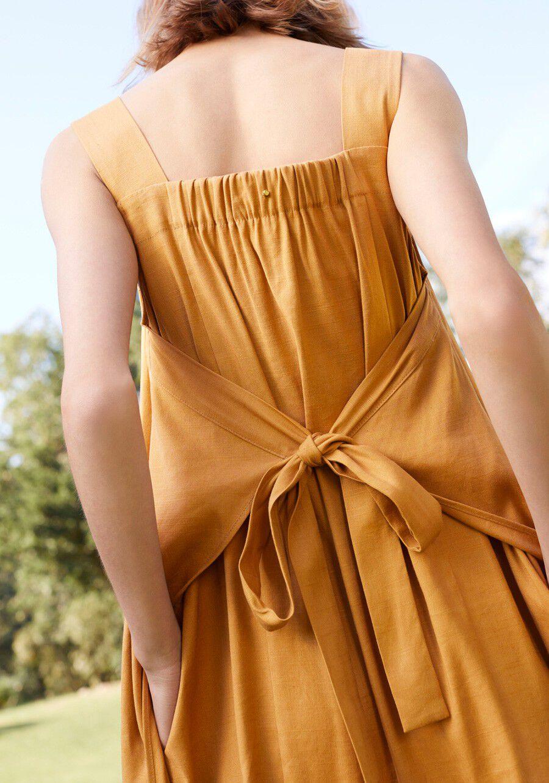 Model wearing Cuyana Linen Tie-Back Dress in Mango