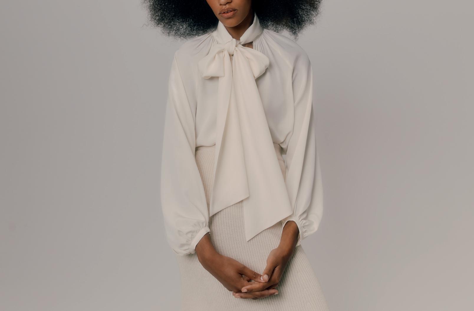 Model wearing Cuyana Bow Blouse