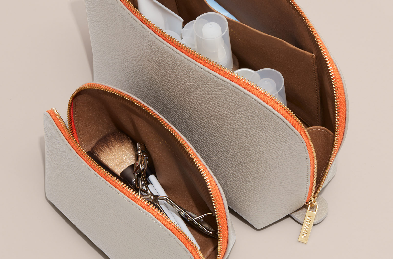 Cuyana Leather Travel Case Set in Stone with toiletries inside