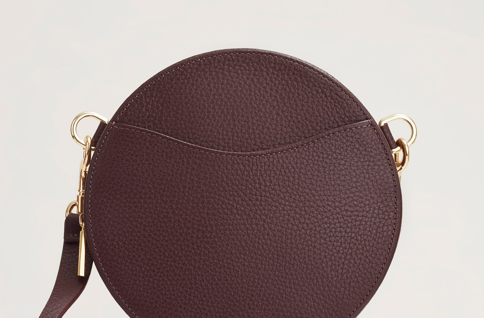 Detail image of curved pocket of Cuyana Mini Circle Belt Bag