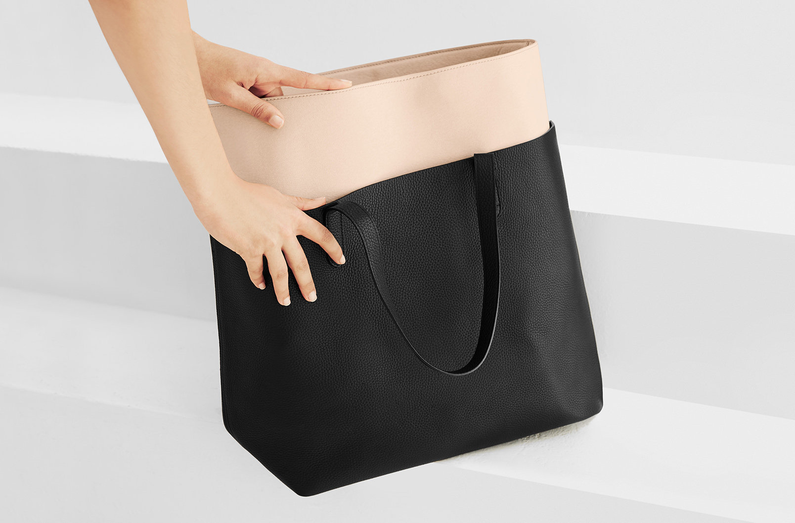 Woman's hands putting Blush Tote Organization Insert going into Classic Leather Tote