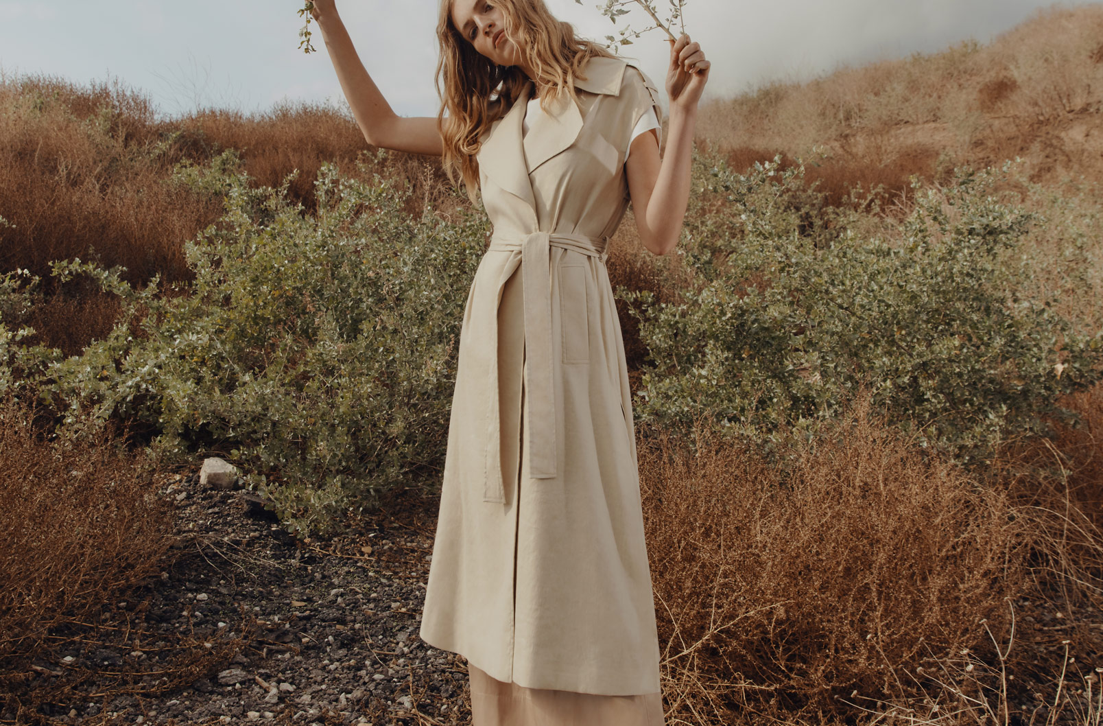 Model wearing Linen Sleeveless Trench in hilly meadow