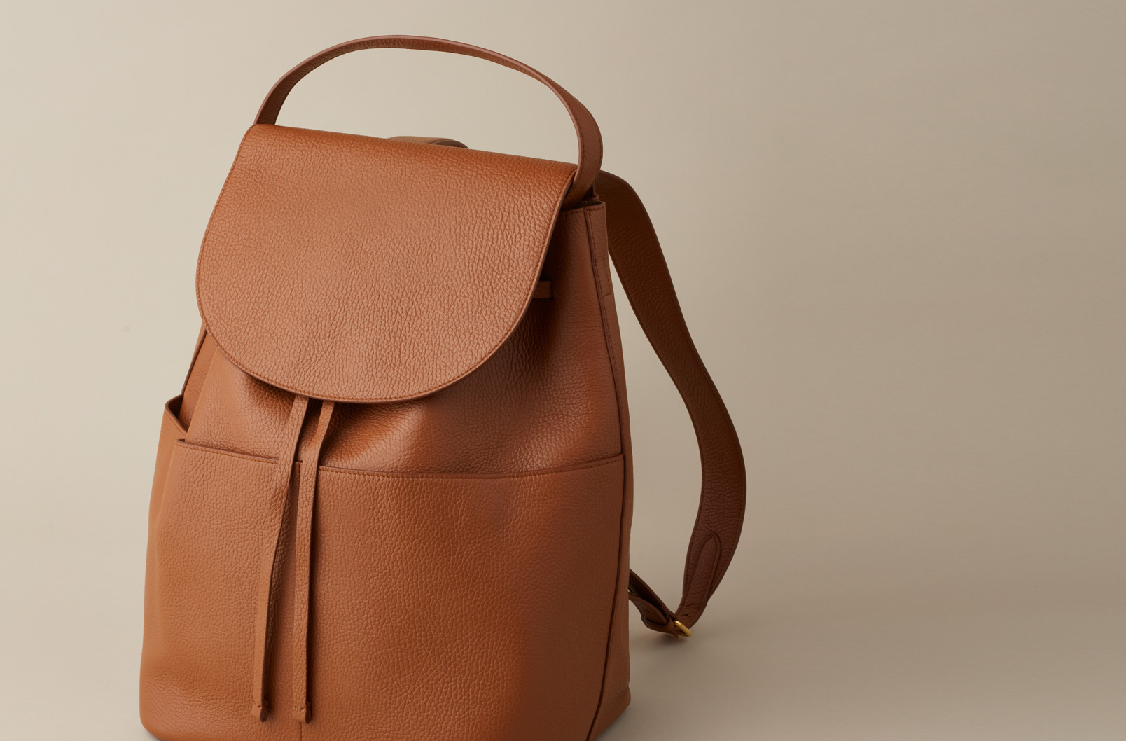 Image showing Large Leather Backpack in Caramel with flap closure, cinch ties, and exterior pockets