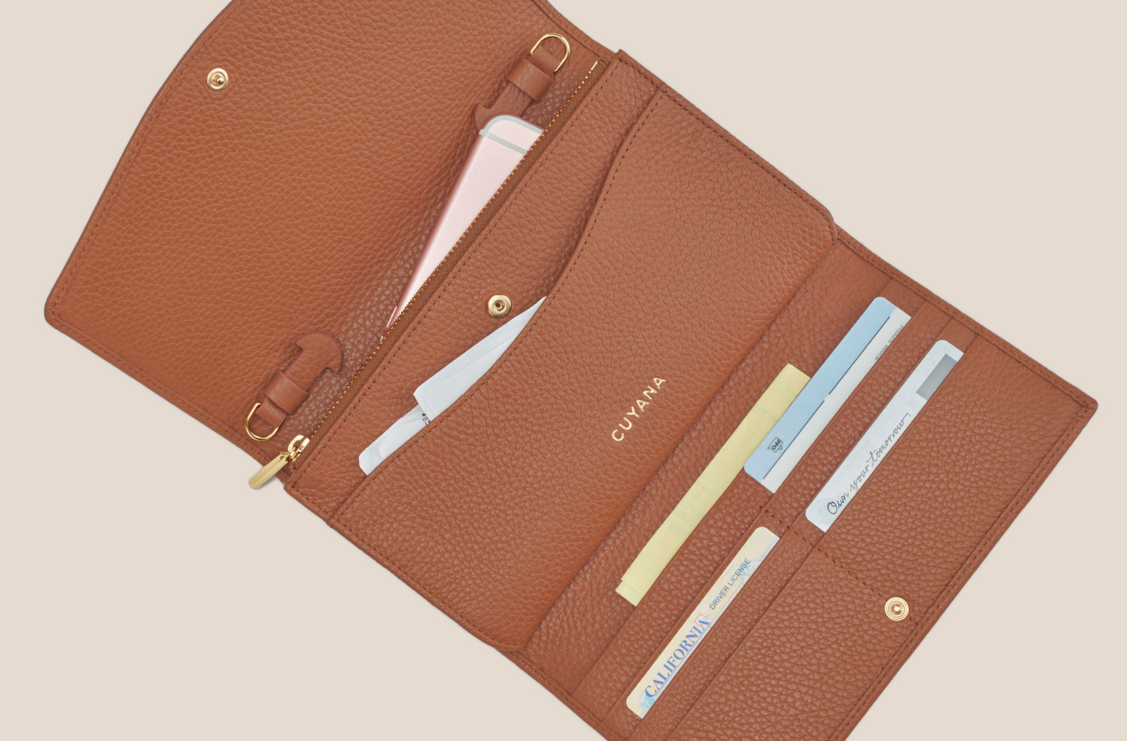 Cuyana Convertible Clutch showing zippered compartments, interior pockets, and credit card slots