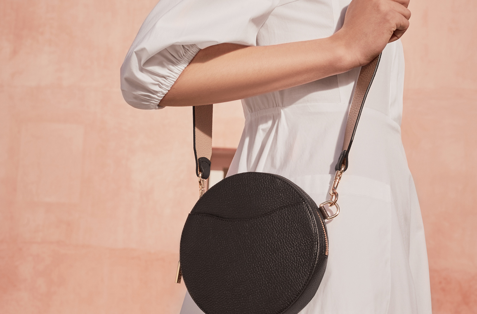 Woman wearing Cuyana Mini Circlet Belt Bag in Black with Wide Strap attached