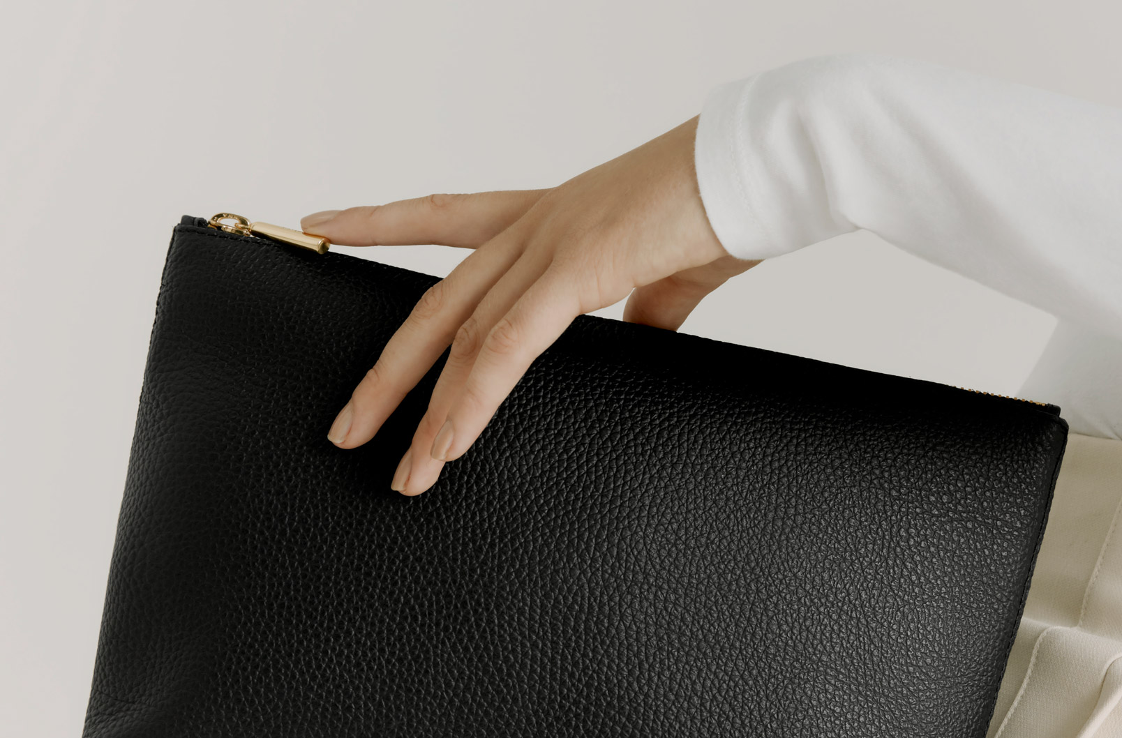 Model's hand with Cuyana Medium Leather Zipper Pouch in Black