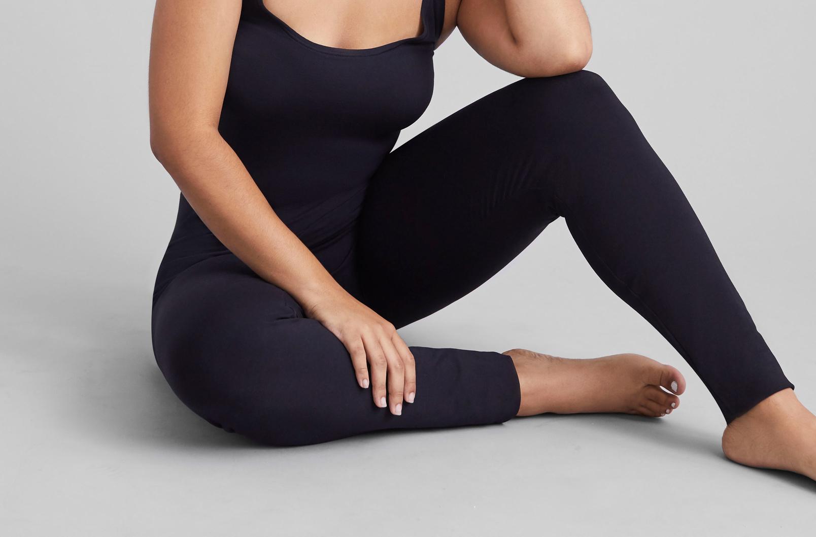 Model sitting and wearing Cuyana Seamless Leggings