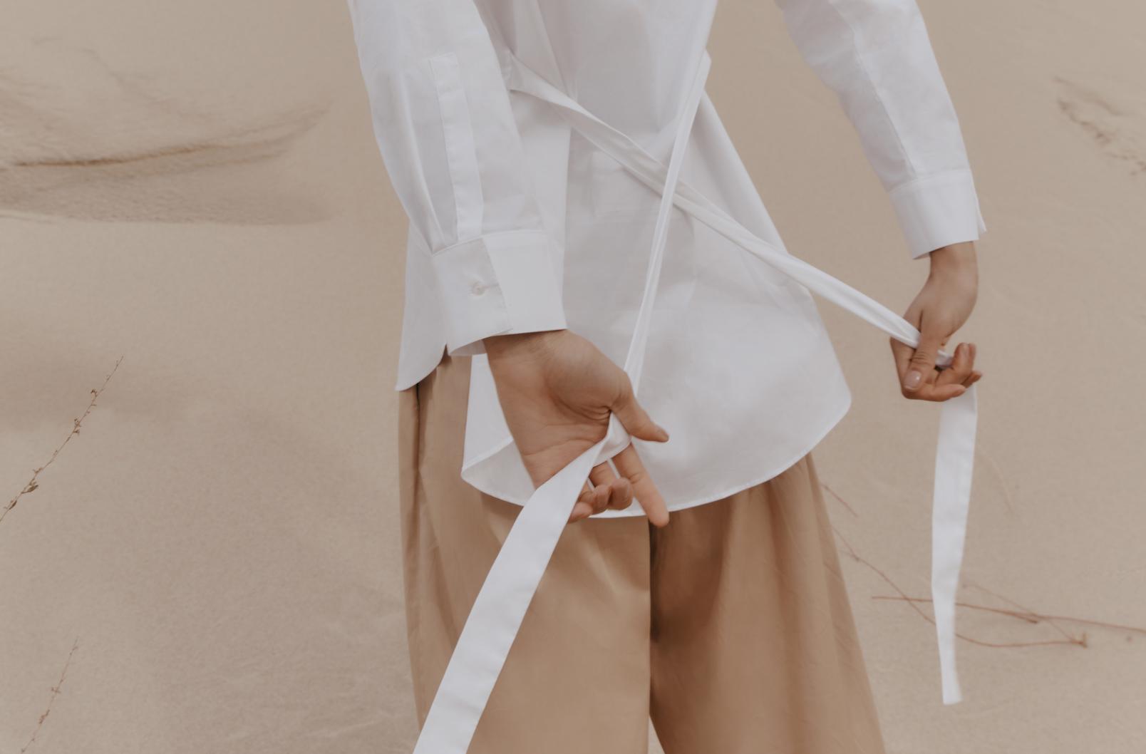 Woman wearing khaki pants with Cuyana Poplin Asymmetrical Shirt showing loose back ties