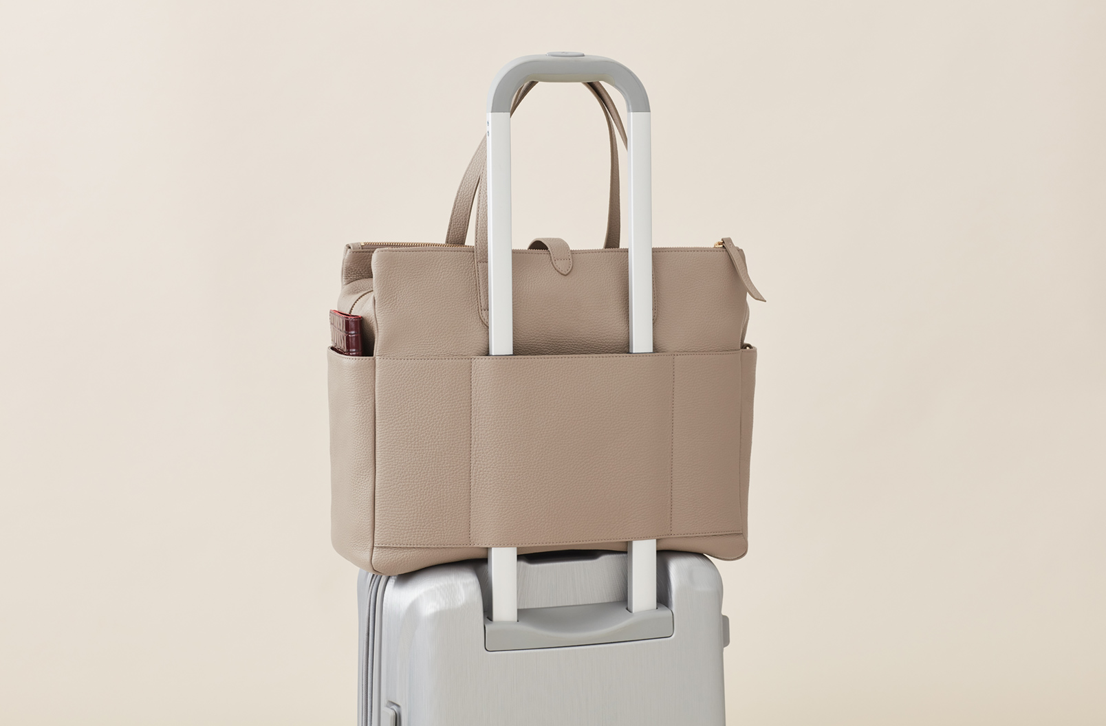 Cuyana Leather Triple Zipper Overnight in Stone on top of suitcase.