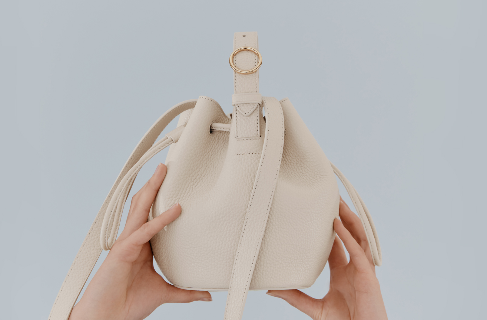Cuyana Mini Drawstring Bucket Bag in Ecru held in air