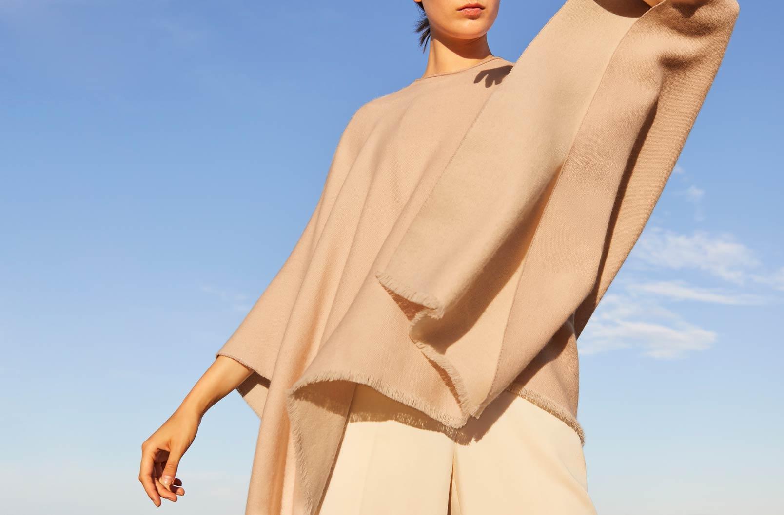 Model wearing Cuyana Blanket Scarf in Camel
