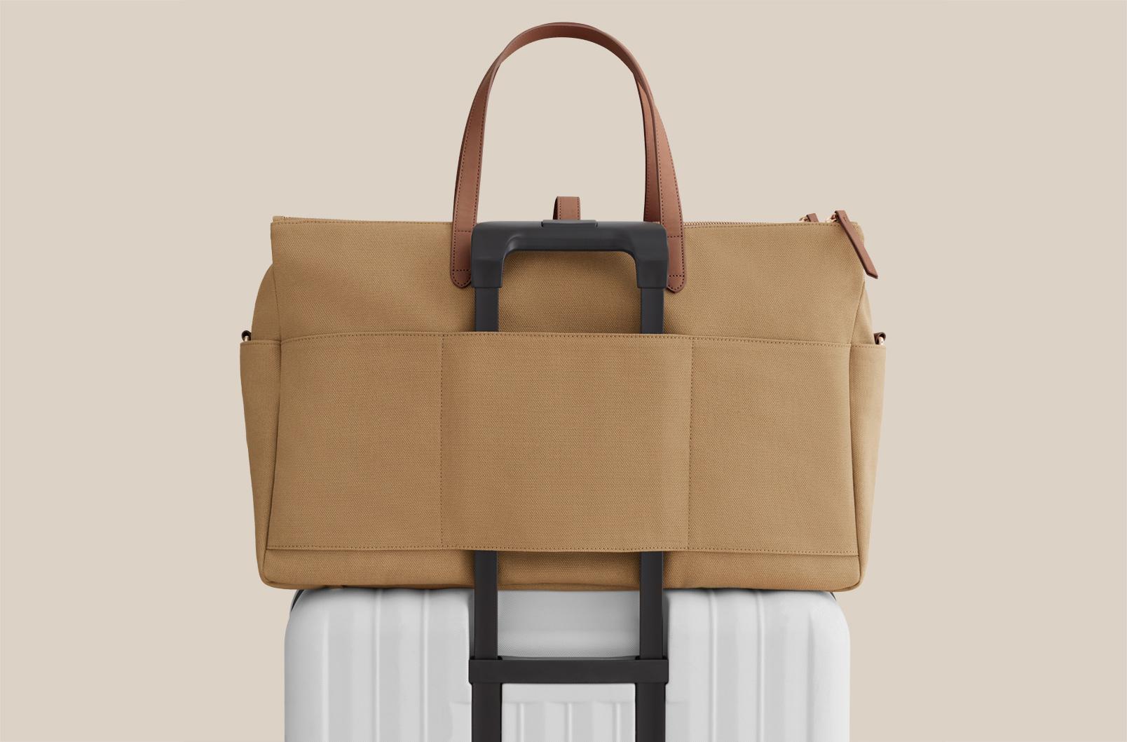Detailed shot of Triple Zipper Weekender luggage sleeve on rolling suitcase handle