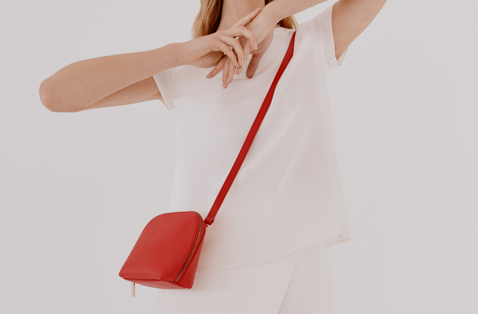 Woman wearing Cuyana Travel Case Crossbody in Red